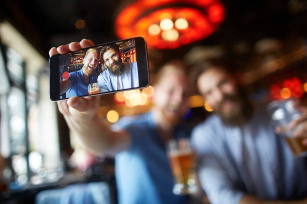 male friends in the bar posing for a selfie - photo messaging stock photos and pictures