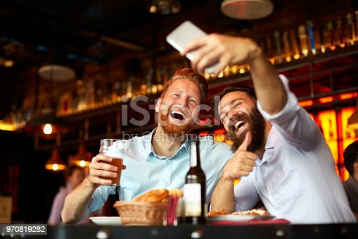 istock Male friends in the bar posing for a selfie 970819282