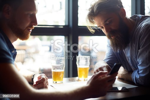 istock Male friends in the bar using mobile smart phone 996005958
