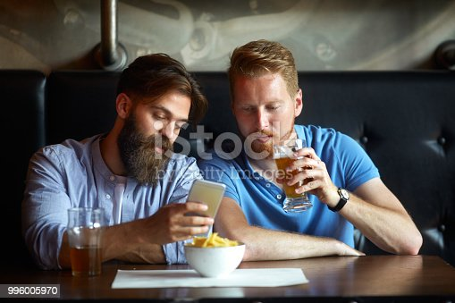 istock Male friends in the bar using mobile smart phone 996005970