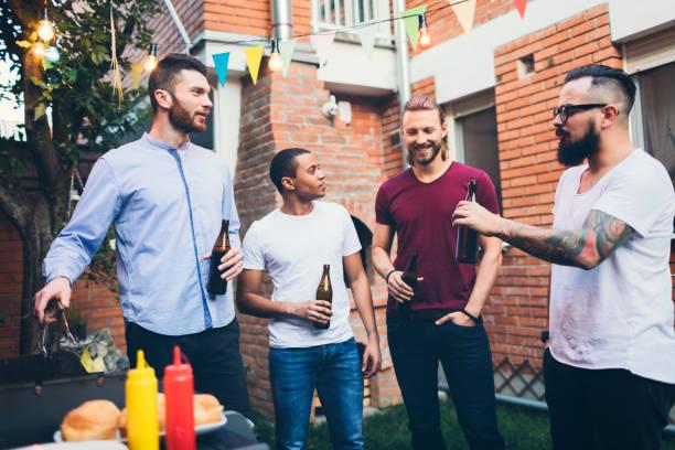 männliche freunde auf einem grill im hinterhof - freundin tattoos stock-fotos und bilder