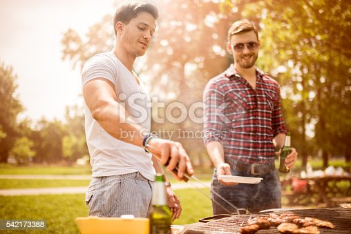 Guys having fun during barbecue picnic in the park or back yard. One of them is holding a plate and beer while the other is cooking and serving.