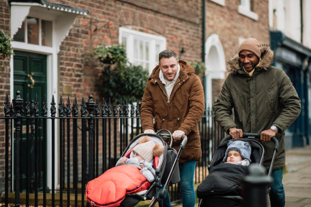 Male Friends Out with Their Babies in Tynemouth, UK Two male friends are out in Tynemouth, North East UK. They are walking on a sidewalk and pushing their baby sons in strollers. They are wearing warm clothing. baby stroller stock pictures, royalty-free photos & images