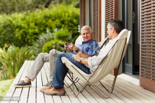 Full length of mature male friends spending leisure time at yard