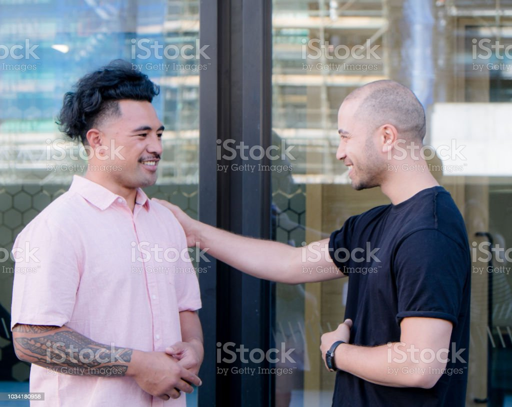 Male friends talking: one is touching the other - possible gay or homosexual theme. In Auckland, New Zealand, NZ stock photo