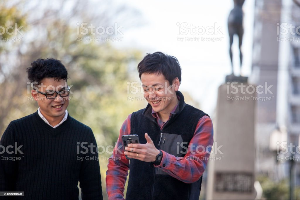 2 male friends walking together stock photo
