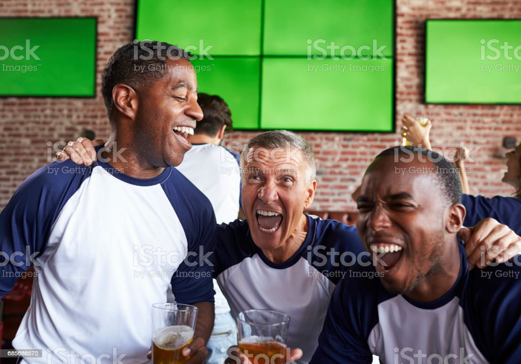 Male Friends Watching Game In Sports Bar Celebrating royalty-free 스톡 사진