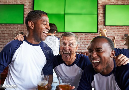 istock Male Friends Watching Game In Sports Bar Celebrating 685688572