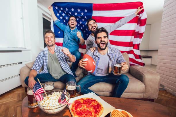 mannelijke vrienden, tv kijken en juichen sport spellen op bank thuis. groep vrienden kijken naar american football wedstrijd. - football friends tv night stockfoto's en -beelden
