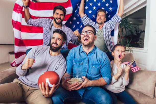 mannelijke vrienden tv kijken en juichen sport games op sofa thuis. groep vrienden kijken naar american football wedstrijd. - football friends tv night stockfoto's en -beelden