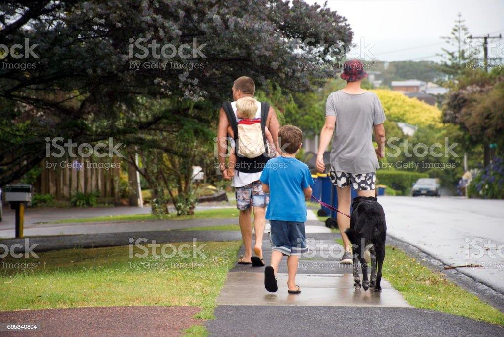 Male Friends with Children walk Dog stock photo