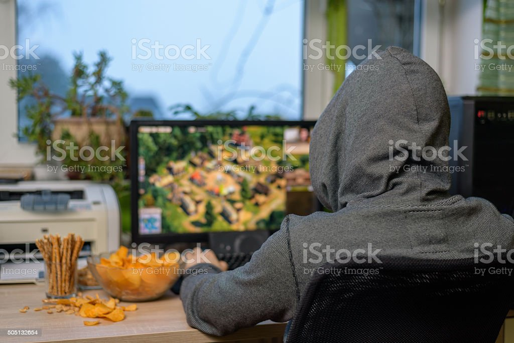male gamer playing strategy game on computer eating snacks stock photo