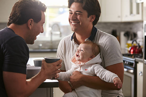 Male gay couple holding baby girl in their kitchen Male gay couple holding baby girl in their kitchen gay person stock pictures, royalty-free photos & images