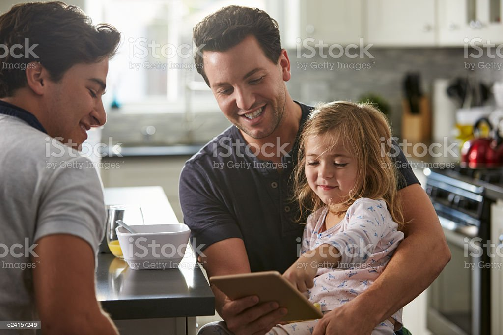 Male gay dads use tablet with daughter in kitchen, stock photo