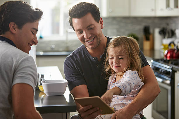 Male gay dads use tablet with daughter in kitchen, Male gay dads use tablet with daughter in kitchen, close up gay couple stock pictures, royalty-free photos & images