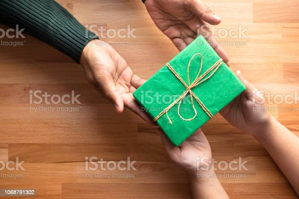 Male gives a gift present to female with wooden copy space moment picture id1068791302?b=1&k=6&m=1068791302&s=612x612&h=mckhbxb0knv44vwquh8hgpyxu0ix uf6h ywcebox m=