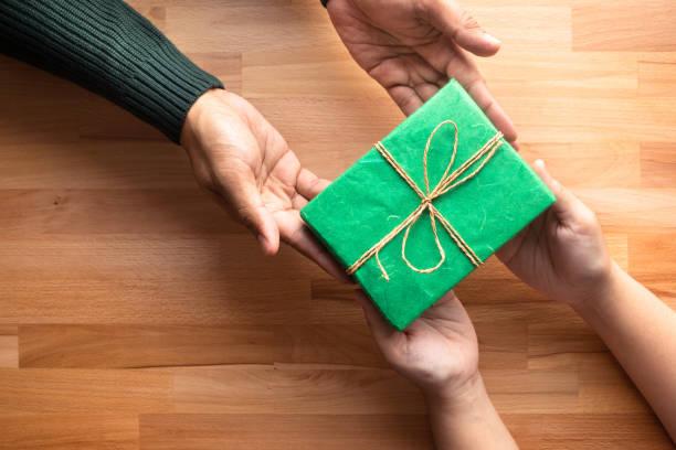 mężczyzna daje prezent dla kobiety z drewnianym tłem przestrzeni kopii.moment szczęścia - gift zdjęcia i obrazy z banku zdjęć