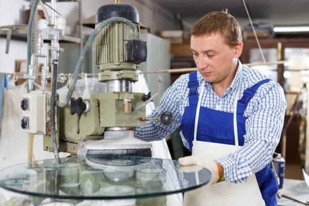 männliche glaser mit assistentin an gebogenem glas abschrägung maschine arbeiten - fensterbauer stock-fotos und bilder