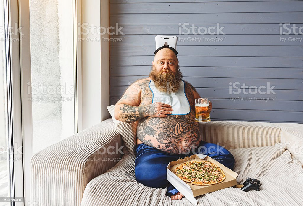 Male glutton eating junk food with alcohol stock photo