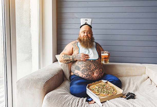 male glutton eating junk food with alcohol - stomach sitting stock photos and pictures