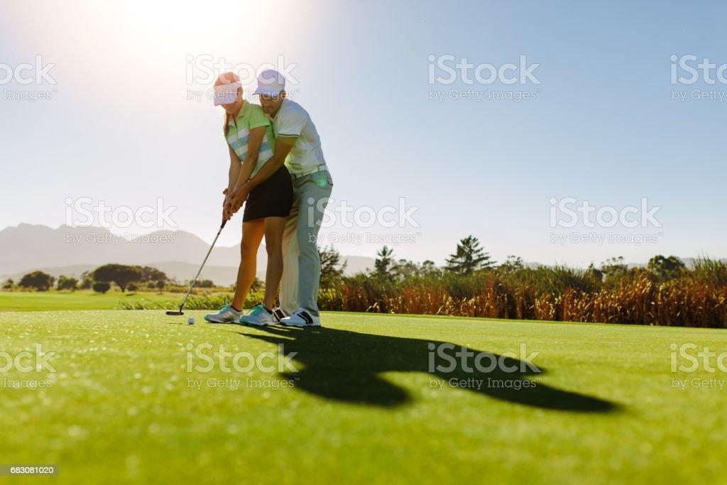 Male golf instructor teaching female golf player foto de stock royalty-free