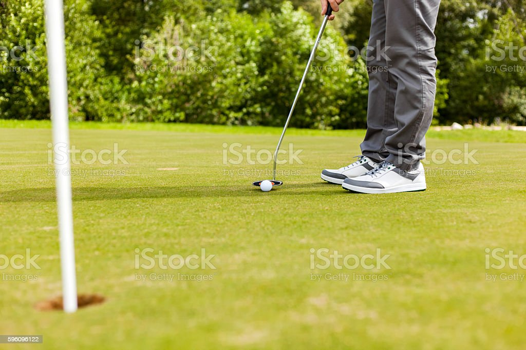 Male golf player drivers ball into the hole royalty-free stock photo