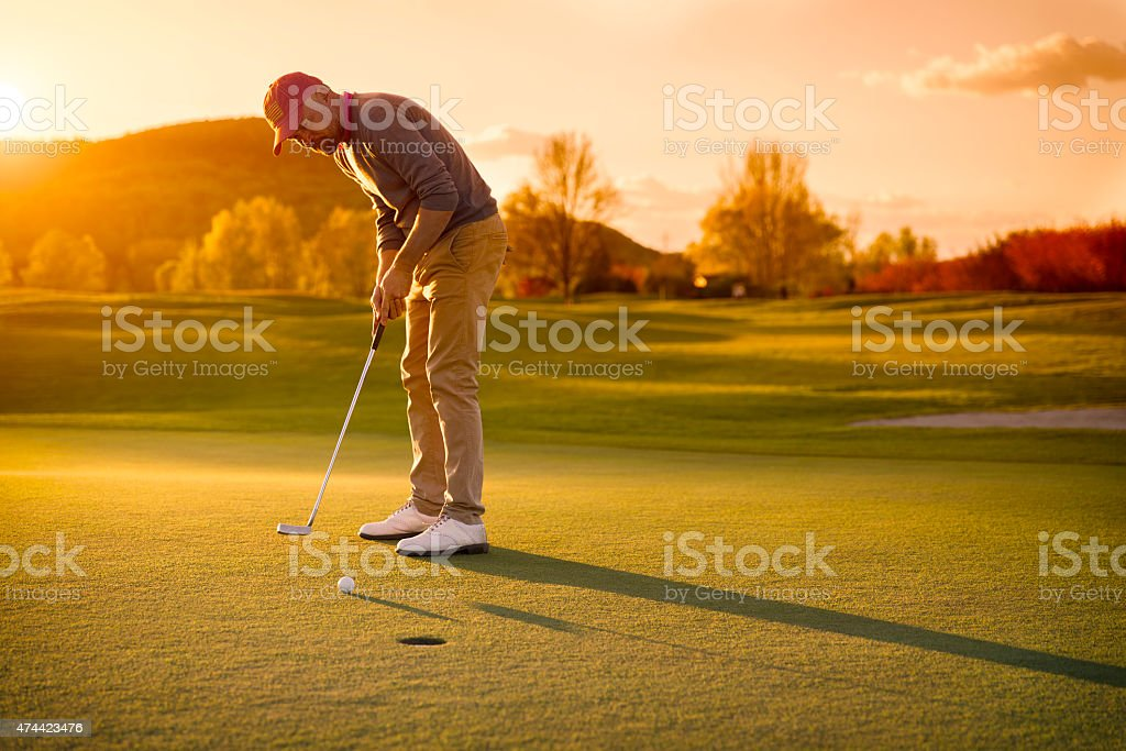 Male golf player putting at sunset. stock photo