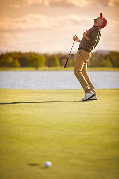 Male golf player shot past hole. stock photo