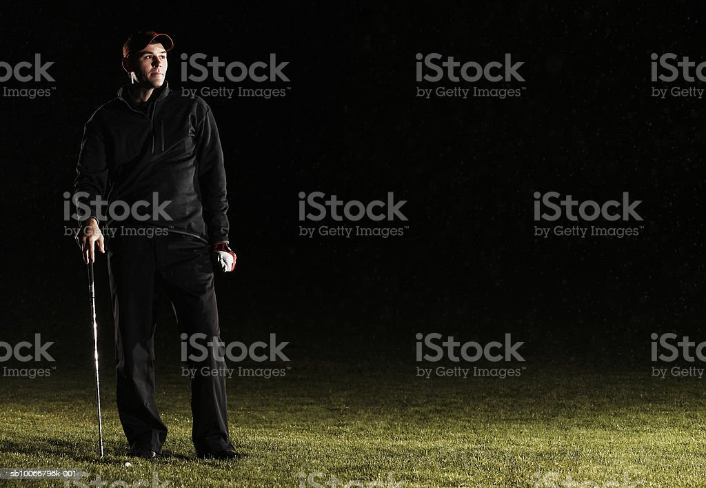 Male golf player standing in golf course, looking away royalty free stockfoto