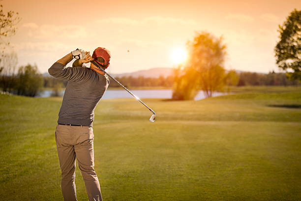 Male golf player swinging golf club at dusk. stock photo