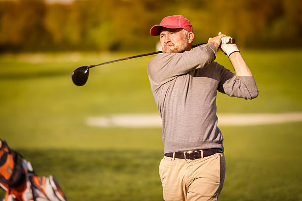 Male golf player teeing off with club. stock photo