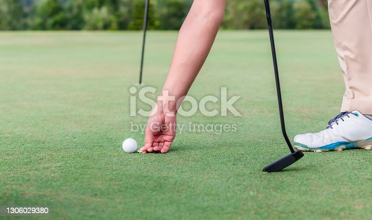 Male golf player using pin marking position of ball golf on green.