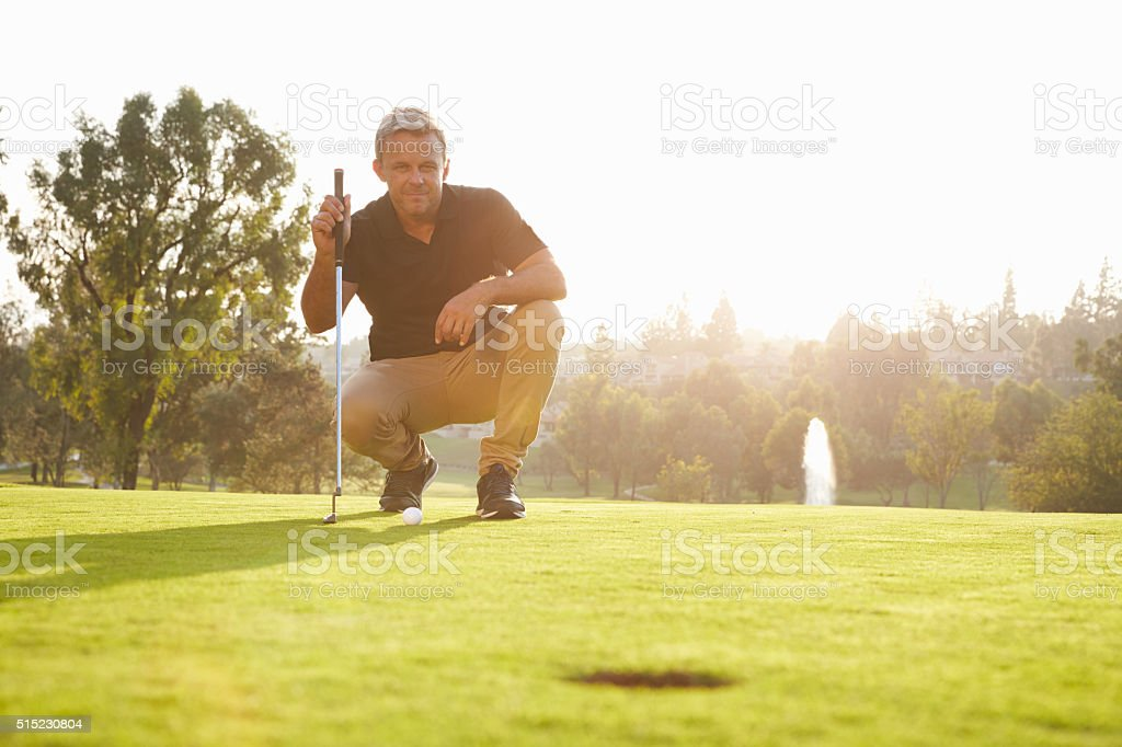 Male Golfer Lining Up Putt On Green stock photo