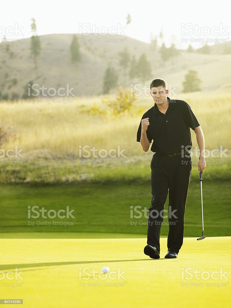 Male golfer sinking put royalty-free stock photo