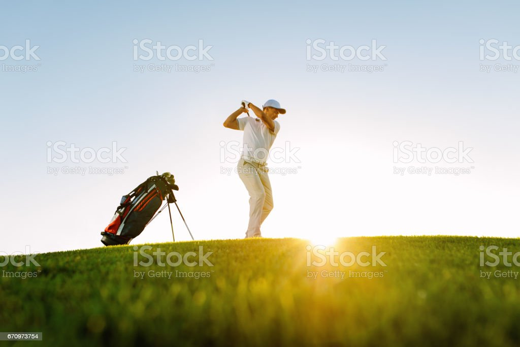 Male golfer taking shot on golf course stock photo