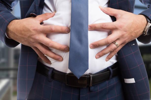 manliga högintressant uppsvälld buk som matsmältningsbesvär problem - matsmältningsbesvär bildbanksfoton och bilder