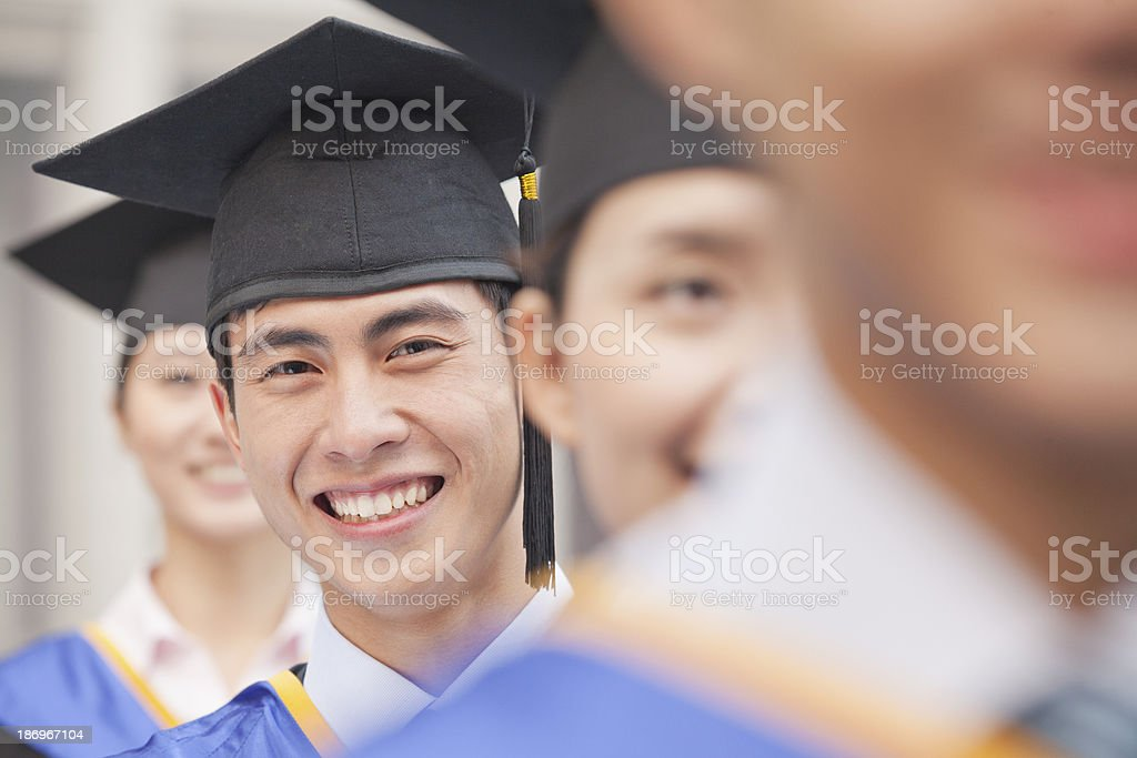 Male Graduate Student Standing in a Row of Graduates stock photo