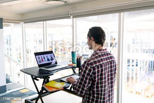 Rear view of Caucasian male graphic designer working on laptop at desk in office