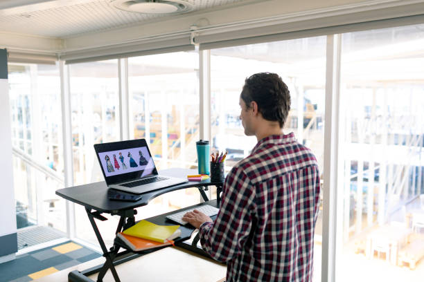 Männlicher Grafikdesigner arbeitet am Laptop am Schreibtisch – Foto