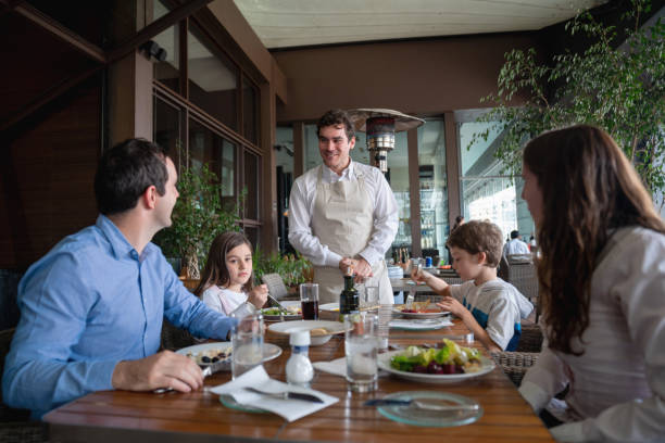 male guest with his family enjoying a meal at the hotel restaurant and ordering something to friendly waiter - being in a relationship with someone is going to require stock photos and pictures
