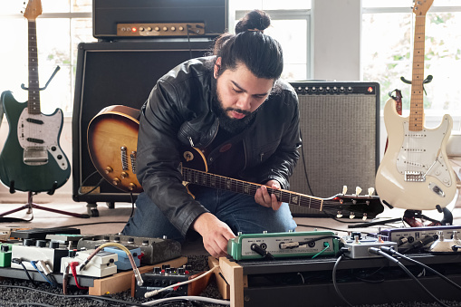 Male Guitarist Surrounded by Sound Equipment Adjusting Sound Effects Pedals