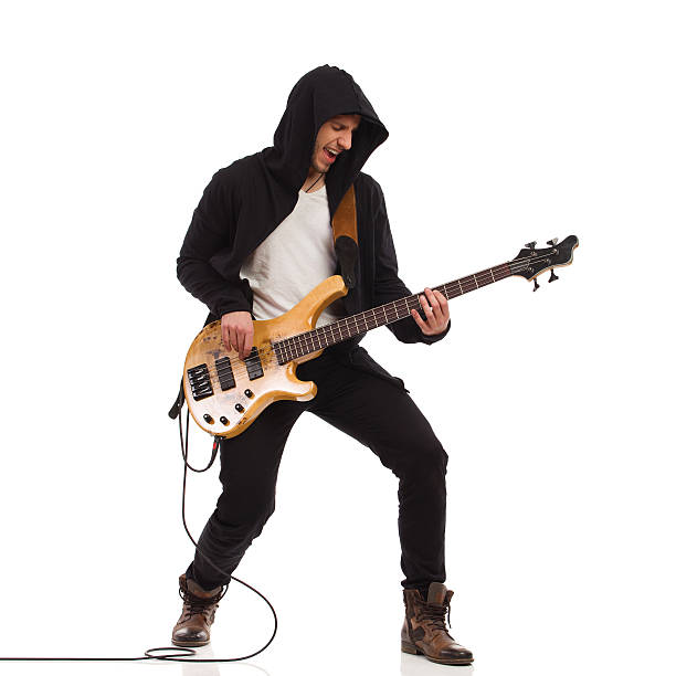 Male guitarist with bass guitar. Shouting guitarist in black hoodie play the bass guitar. Full length studio shot isolated on white. guitarist stock pictures, royalty-free photos & images