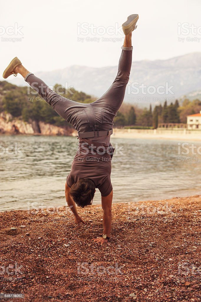 Male guy doing headstand at the beach stock photo
