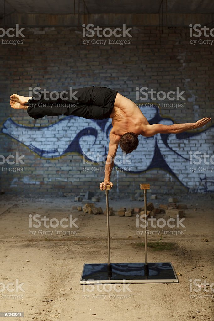 Male gymnast balancing on a metal rod with a block stock photo