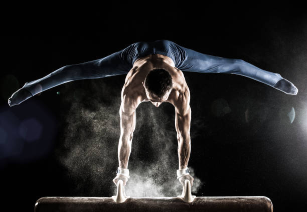 male gymnast doing handstand on pommel horse - agile stockfoto's en -beelden