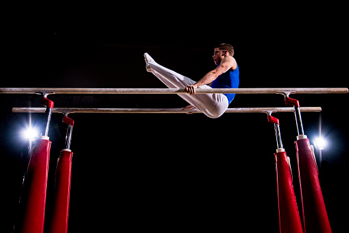 Young male gymnast performing on parallel bars in sports hall.