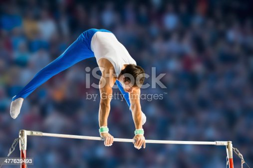 Side view of young man performing short routine on horizontal bar, artistic gymnastics