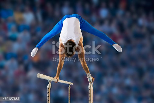 Rear view of young man performing short routine on parallel bars, artistic gymnastics