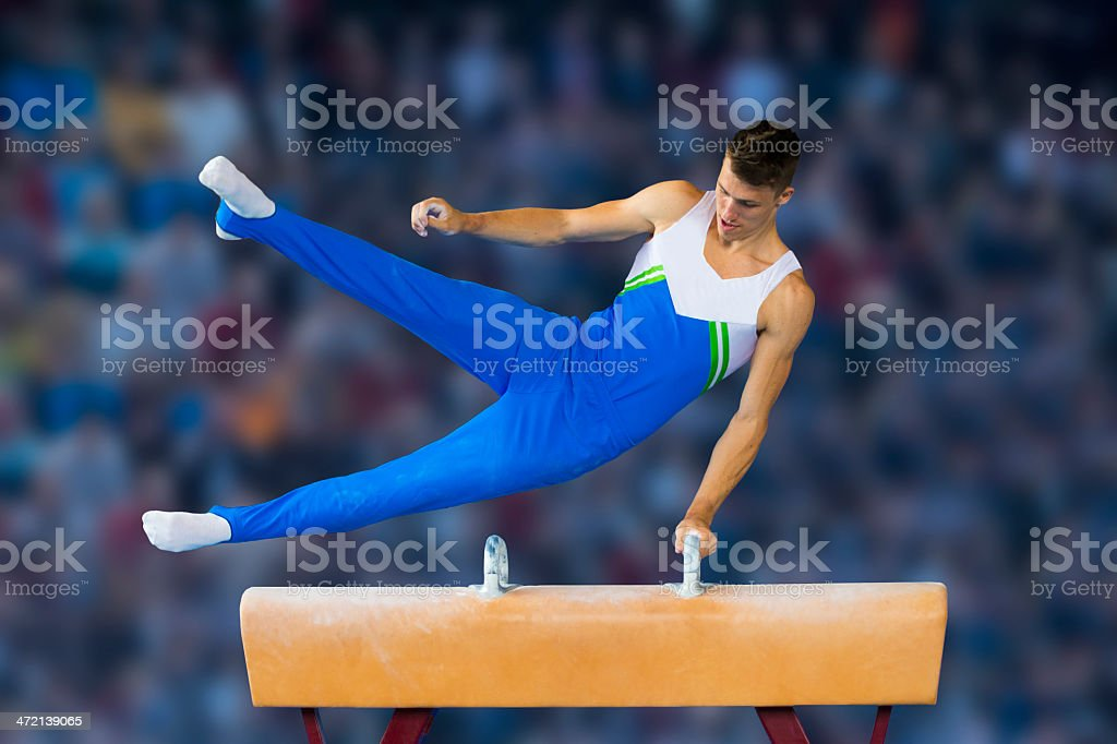 Male gymnast performing routine on the side horse stock photo
