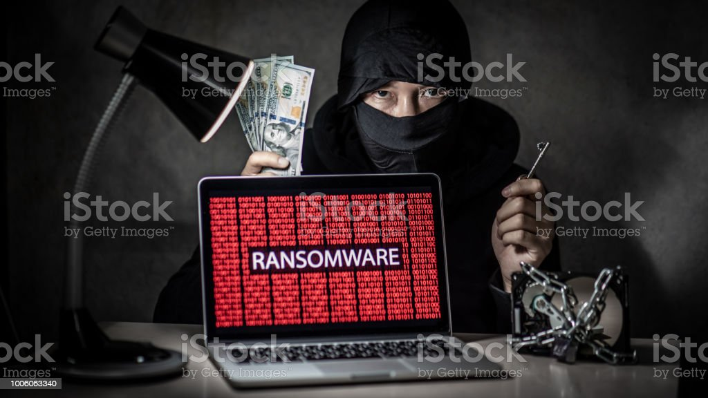 Male hacker holding key and dollar banknote with laptop computer...